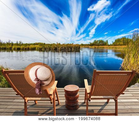 Lovely place to relax. Two beach chairs and hat on the riverbank. Cirrus clouds are reflected in the Winnipeg River. Old Pinawa Dam Park. The concept of recreational tourism