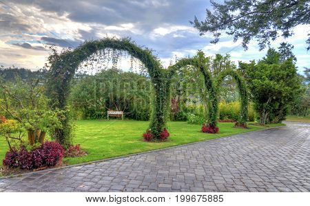 Public park with a beautiful garden made with flowers, trees, plant arches, benches and stone floors. Outskirts of Quito, Pichincha, Ecuador.