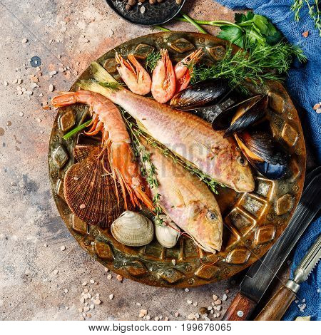 Fish, shrimp, clams on plate at table with blue cloth, spices, knives