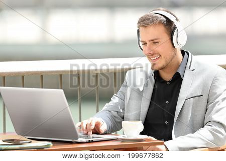 Portrait of an executive wearing headphones working on line sitting in a coffee shop