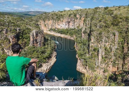 Man Sits On A Rock Overlooking A Canyon With A River On The Bottom And Rocky Walls Covered By Green