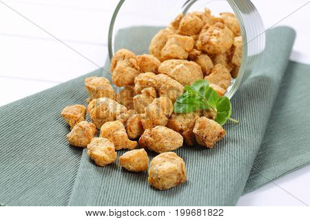 glass of soy meat cubes spilt out on grey place mat - close up