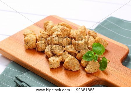pile of soy meat cubes on wooden cutting board - close up