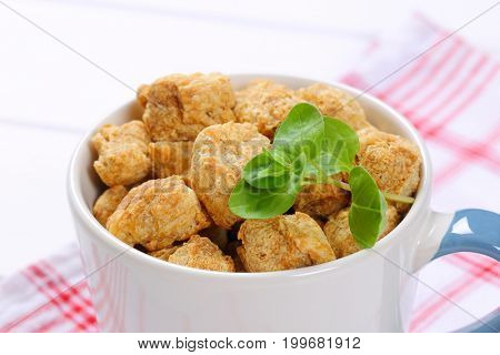 mug of soy meat cubes on checkered dishtowel - close up