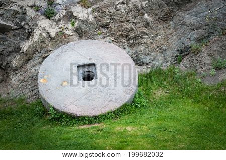 Stone granite wheel with rusted metal rim isolated on green grass