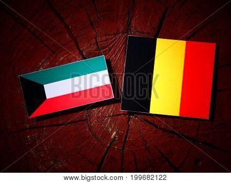 Kuwaiti Flag With Belgian Flag On A Tree Stump Isolated