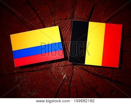 Colombian Flag With Belgian Flag On A Tree Stump Isolated