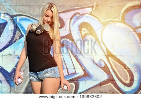 A Young And Beautiful Sexy Girl Graffiti Artist With A Paint Spray And Gas Mask On Her Neck Stands O