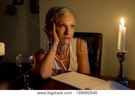 thoughtful woman is writing a letter under candle light
