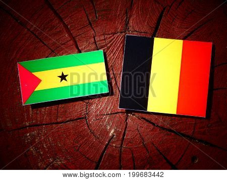 Sao Tome And Principe Flag With Belgian Flag On A Tree Stump Isolated