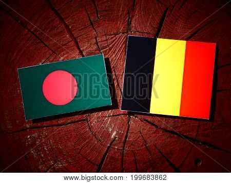 Bangladesh Flag With Belgian Flag On A Tree Stump Isolated