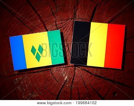 Saint Vincent And The Grenadines Flag With Belgian Flag On A Tree Stump Isolated