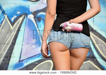 A Rear View Of A Young And Beautiful Sexy Blonde Girl Graffiti Artist With A Paint Spray Stands On T