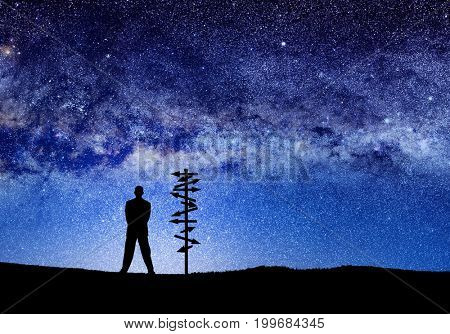 conceptual image of silhouetted directional sign and businessman over abstract lights of universe