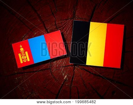 Mongolian Flag With Belgian Flag On A Tree Stump Isolated