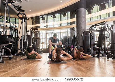 Fitness instructor timing three young people doing lateral crunch exercise with raised legs for abdominal muscles indoors at the gym