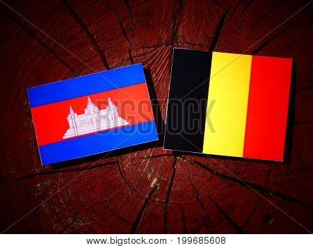 Cambodian Flag With Belgian Flag On A Tree Stump Isolated