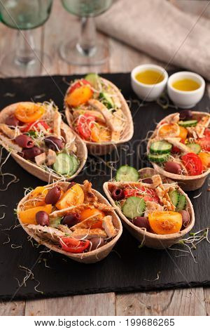 Tortillas with grilled chicken meat, cherry tomato, cucumbers, calamata olives, and radish sprouts on a rustic table