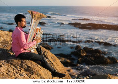 Musician play to musical instrument Tuba on romantic sea shore.