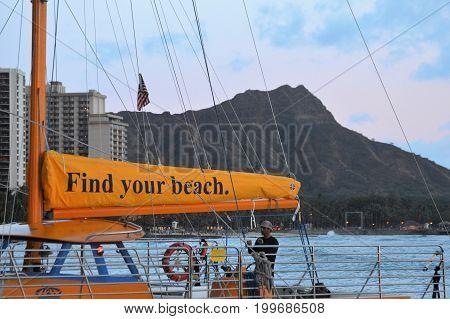 HONOLULU, HI - JUNE 30, 2017 : unknown man prepares tourist boat at Waikiki Beach with Diamond Head background