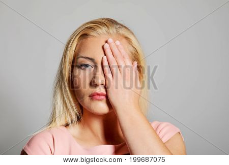 A picture of a young woman covering her face.