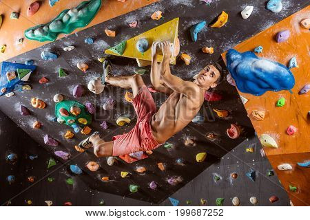 Young man bouldering in indoor climbing gym looking at next handhold to grip