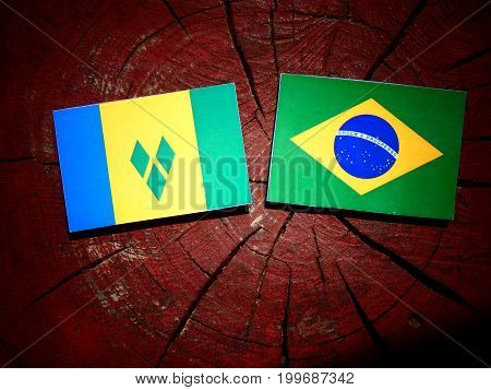 Saint Vincent And The Grenadines Flag With Brazilian Flag On A Tree Stump Isolated