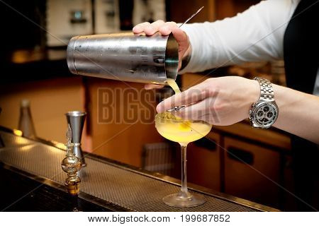 Bartender is pouring cocktail from shaker into the glass, toned image