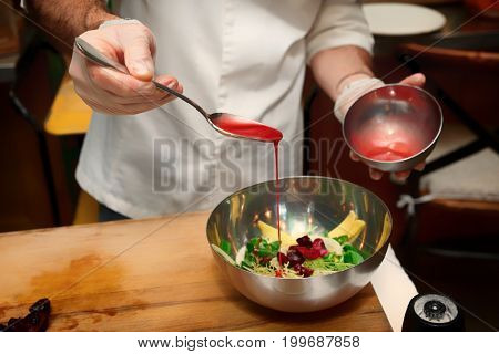 Chef is adding sauce to bowl with vegetable appetizer, professional cooking, toned image