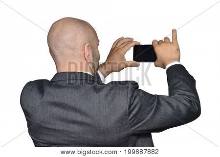 Back view from a bald head businessman taking picture with smart phone.