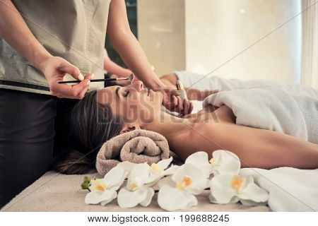 Relaxed woman lying down on massage bed during facial treatment at Asian spa and wellness center