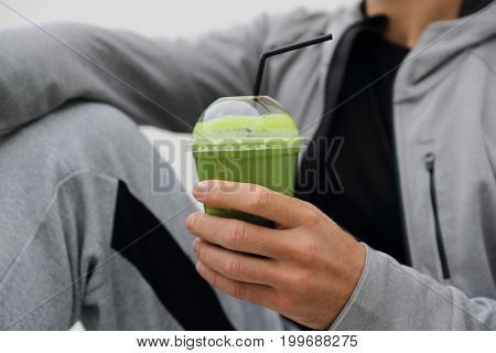 Green smoothie detox man drinking vegetable juice cleanse. Sport athlete holding plastic cup breakfast drink closeup.