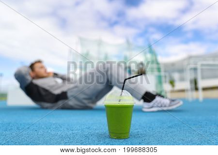 Fitness man training at gym with green smoothie detox drink doing sit-ups exercises on floor outdoors.