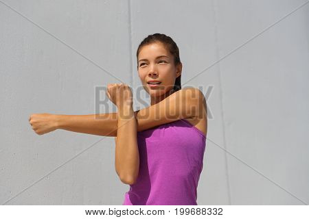 Fitness Asian runner doing warm-up stretching arms before jogging workout outdoor. Run race girl getting ready for running competition.