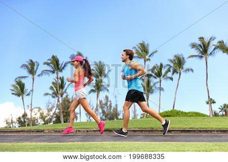 Sport fitness couple lifestyle. Healthy people running together in summer park outdoor, runners training cardio.