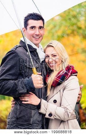 Couple enjoying fall day having walk despite the rain, the foliage is colorful