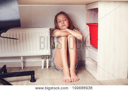 Sad child at home. Abuse. Depression girl indoors