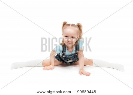 Beautiful little girl making splits isolated on white background