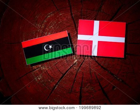 Libyan Flag With Danish Flag On A Tree Stump Isolated