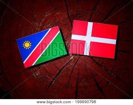 Namibian Flag With Danish Flag On A Tree Stump Isolated