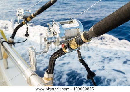 Close up of salt water rod and reel fishing gear in rod holders with safety lines attached to boat rails.