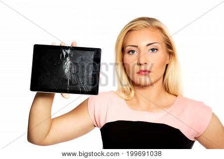 Upset young woman is holding broken tablet.