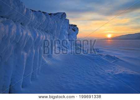 Ice wall of frozen rocks on sunset background, beautiful winter landscape