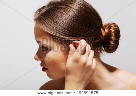 Closeup up of woman having ear pain and touching her painful ear.