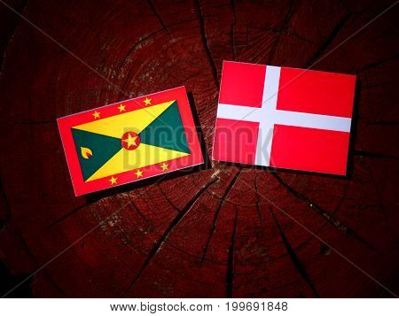 Grenada Flag With Danish Flag On A Tree Stump Isolated