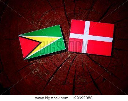 Guyana Flag With Danish Flag On A Tree Stump Isolated