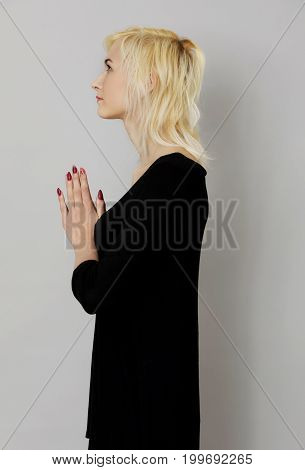The portrait of woman praying with hands together.