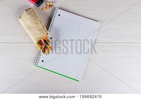Blank notepad and pencil color on wooden blackground Notebook colored pencils