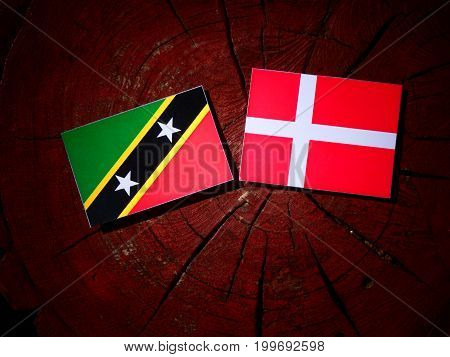 Saint Kitts And Nevis Flag With Danish Flag On A Tree Stump Isolated
