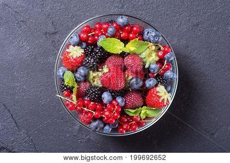 berries : raspberries blueberries blackberries strawberries in a bowl . Top view